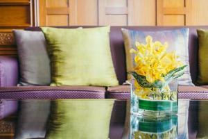 vasblomma på bordet med kudde på soffan foto