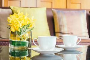 vasblomma och vit kaffekopp på bordet och kudde på soffan foto