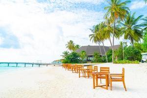tomt träbord och stol på stranden med havsutsikt bakgrund i Maldiverna foto