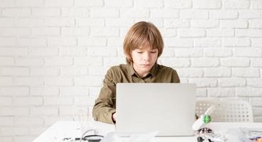 ung pojke som arbetar eller studerar på den bärbara datorn hemma foto