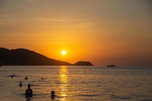 människor som simmar i den vackra solnedgången på Patong Beach, Phuket, Thailand foto