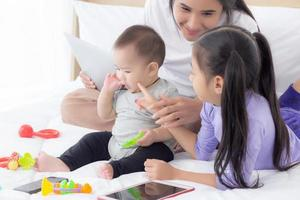 ung asiatisk mamma och babyflicka som ligger och leker på sängen tillsammans, mamma och dotter, familj av känslor och uttryck med lycklig, förälder och nyfödd slappna av och positivt, känslor och uttryck. foto