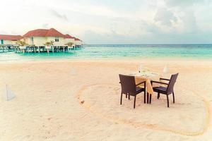 tomt matbord och stol på stranden med havsutsikt bakgrund i Maldiverna foto