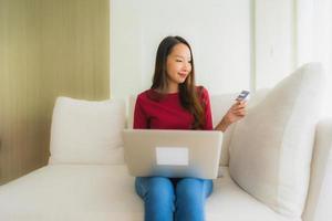 stående vackra unga asiatiska kvinnor som använder datorbärbar dator med mobiltelefon och kreditkort foto