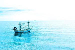 liten fiskebåt som flyter i blått hav med blå himmel, thailandfiskebåt eller fiskebåt eller fartyg på sam roi yod bech prachuap khiri khan thailand med blå himmel och moln och blått hav foto