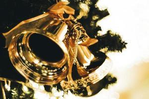 gyllene klockor med en röd rosett på julgransuddar ljus bokehbakgrund foto