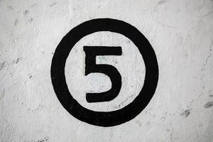 nummer fem på en vit vägg foto