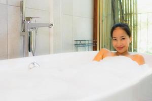 stående ung vacker asiatisk kvinna ta ett bad i badkaret foto
