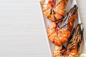 grillade tigerräkor eller räkor med citron på en tallrik foto