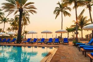 vacker palm med paraplystol pool i lyxhotell semesterort vid soluppgångstider - semester och semester koncept foto