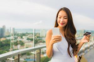 stående vacker ung asiatisk kvinna glad och ler med kreditkort och mobil eller smart telefon och shoppingväska foto