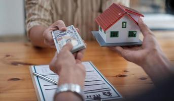 fastighetsmäklare med husmodell på hans erbjudandehus. fastighetsförsäkring och säkerhetskoncept foto