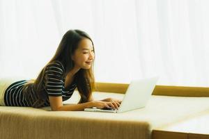 stående härlig ung asiatisk kvinna som använder datoranteckningsboken eller bärbar dator på soffan i vardagsrummet foto