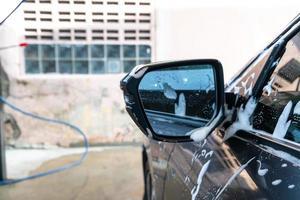 närbild bil sidospegel med bil tvätt skum foto