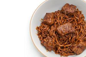 jjapaguri eller chapaguri koreanska svarta bönor kryddiga nudlar med nötkött på vit bakgrund foto