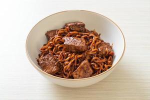 jjapaguri eller chapaguri koreanska svarta bönor kryddiga nudlar med nötkött foto