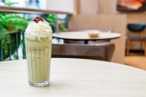 matcha grönt te latte blandad med vispad grädde och röd böna i kafé och restaurang foto