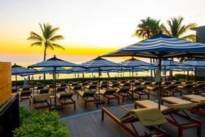 paraplyer och stolar runt utomhuspoolen på hotellresorten för semesterresor bakgrund foto