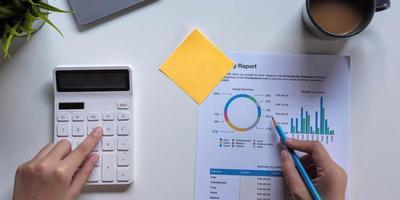 kvinna med ekonomisk rapport och miniräknare. kvinna som använder miniräknare för att beräkna rapporten vid bordet i regeringsställning foto