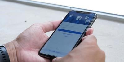 chiang mai, thailand 18 maj 2021 - kvinna som håller en iPhone x med social internet-tjänst facebook på skärmen. foto