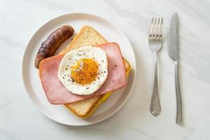 hemlagat bröd rostad ost, toppad skinka och stekt ägg med fläskkorv till frukost foto