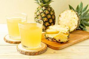 färsk ananasjuice på träbakgrund foto