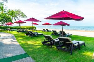 strandstolar och paraplyer med havsstrandbakgrund foto