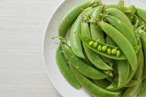 färska söta gröna ärtor på den vita plattan foto