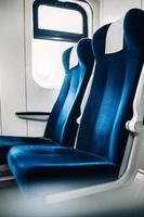 en rad mjuka stolar med hög rygg vid fönstret i tågvagnen - en bekväm åktur foto