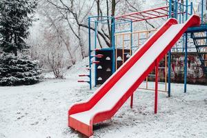 snötäckt baby gunga på vintern - tom lekplats - röd plast gungstol i kylan foto