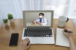 kvinnapatient som får feber och hosta som misstänks för covid-19 eller coronavirusinfektion, kontakta asiatisk läkare via vdo-samtal. telemedicin och nytt normalt livsstilskoncept foto