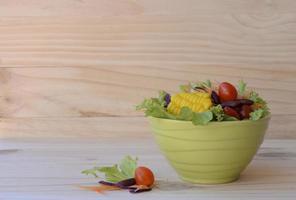 färsk grönsaksallad för hälsokost på träbakgrunder foto