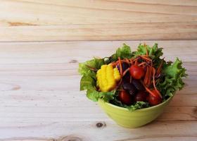 färsk grönsaksallad på träbakgrunder foto
