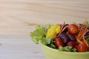 närbild av grönsaksallad att äta på träbakgrunder foto
