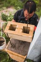 händerna på en professionell murare medan du arbetar på en byggarbetsplats - murvägg från ett betongblock foto