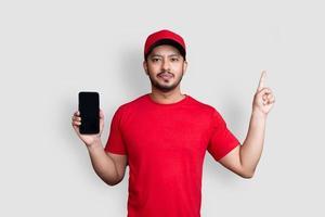 leverans man anställd i röd keps tom t-shirt enhetlig håll svart mobiltelefon applikation isolerad på vit bakgrund foto
