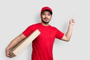 leverans man anställd i röd mössa tom t-shirt finger enhetlig hålla Tom kartong isolerad på vit bakgrund foto