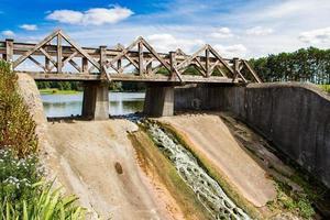 gammal fördämning med en träbro. utsikt över sommarlandskapet. foto