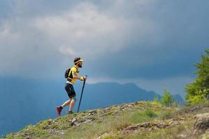 manlig idrottare klättrar lutningen på berget under träning i bergmaraton foto