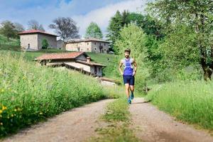 ung idrottsman kör i landsbygdens kulle landskap foto