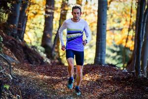 professionell idrottsman löpare tränar bland skogen foto