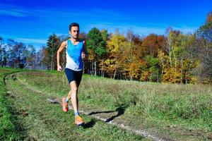 springande idrottsman under ett träningspass bland ängar och skogar på sluttningar foto