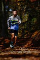 springande idrottare under maratonförberedelsetåg i höstskogen foto