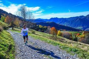en mountain running idrottare tränar på grusvägen foto