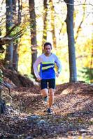 professionell springande idrottare tränar bland lövskogen foto