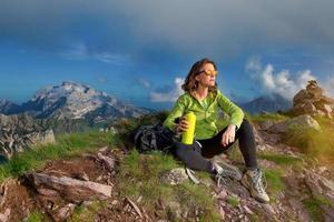 en flicka vilar efter att ha klättrat på toppen av ett berg foto