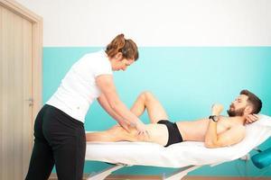 en idrottsman under en massör och sjukgymnastbehandling vid quadriceps foto