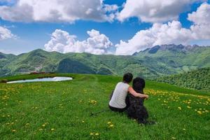 en flicka med sin stora hund tittar på landskapet i bergen foto