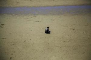 kvinna sitter på stranden foto