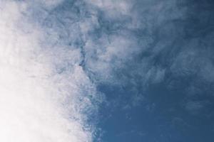 djupblå himmel och höga moln i solstrålarna vid solnedgången foto
